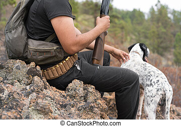 close up view of an unrecognizable hunter and his dog in the forest.