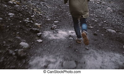Close-up view of anxious male foot in boots running away from somebody through the rocky way in Iceland.