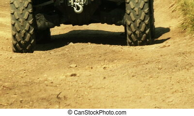 Close up view of ATV wheels in terrain.