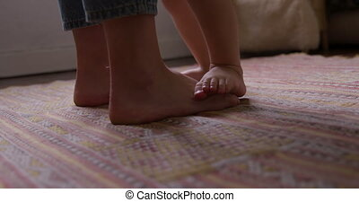 Close up view of baby and mother foot at home - Side view ...