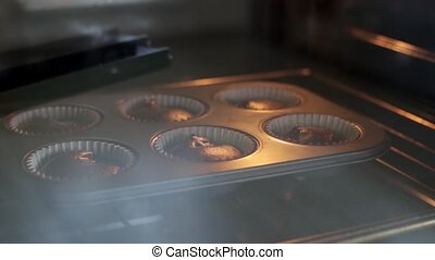 Close-up view of baking dish with chocolate cupcakes. Time lapse of growing of the dough, muffins in baking tray.