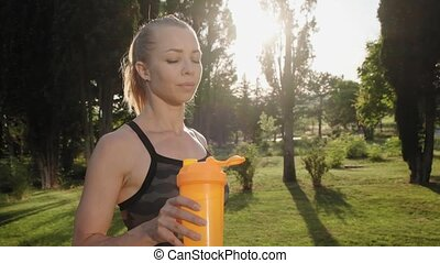 Close up view of beautiful blond female model drinks water...