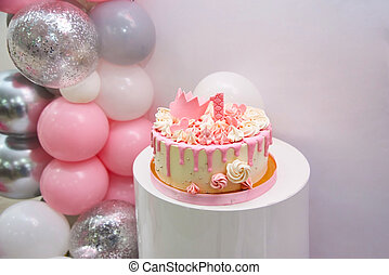Close up view of birthday cake 1 year. Sweet pink cake with decor for girl, a princess gold crown and number 1 on white background with place for text. Anniversary first birthday with helium balloons.