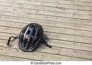 Close up view of black helmet for active sports on wooden background isolated. Sweden.
