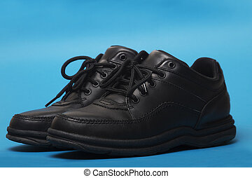 black shoes isolated on a blue background