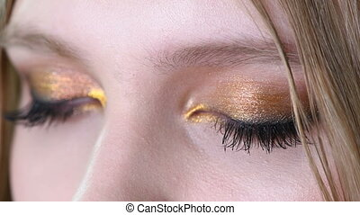 Close up view of blue woman eye with beautiful golden shades...