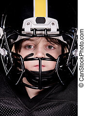 boy american football player in helmet looking at camera