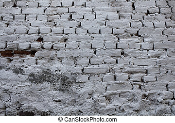 Close up view of brick wall background covered with white plaster.