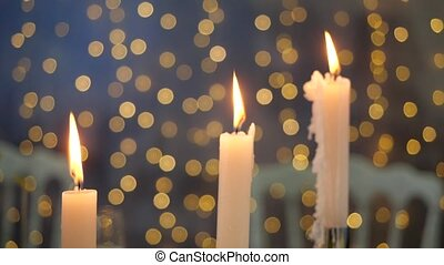 Close-up view of burning candles on a background of blurry flickering lights. Bright beautiful background in form of lights for three candles. Beautiful scenery for the new year in a cozy atmosphere.