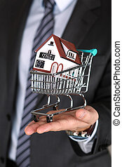 Close-up view of business man's hand holding shopping cart with small house model