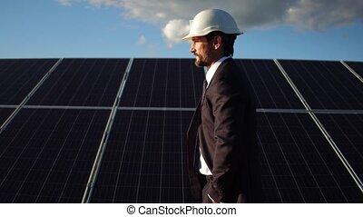 Close up view of chief executive walkig through solar panels.