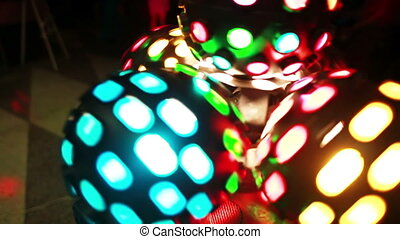 Close-up view of colored light disco ball twisting. Colored show at the disco club party. Rays of the scene light.