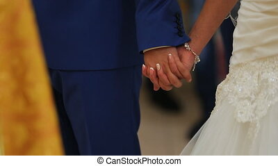 Close up view of couple holding hands having wedding ceremony in church.