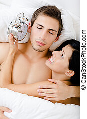 Close up view of couple lying in bed with alarm clock