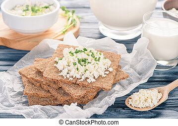 close-up view of crackers with cottage cheese on wooden table