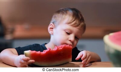 Close-up view of cute little boy sitting at the table on the kitchen. Male holding a piece and eating a watermelon.