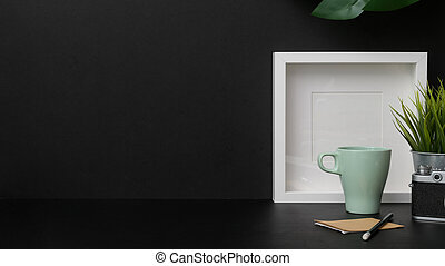 Close up view of dark modern workplace with mock up frame, camera and coffee cup