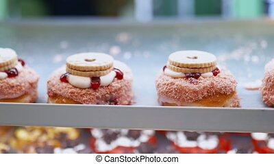 Close up 4k view of doughnuts covered with pink strawberry-flavored topping and with cookies on top, displayed on a metal tray above more colorful doughnuts at a bakery