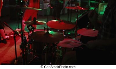 Close-up view of drummer plays on stage. Concert rock band in a nightclub or prom. Man uses a musical instrument.