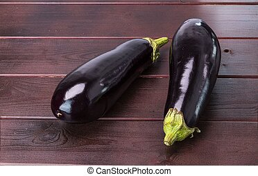 Close up view of eggplants isolated on brown wooden background. Healthy food concept.