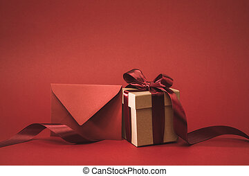 close up view of empty envelope and present with ribbon isolated on red