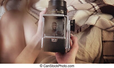 Close-up view of european woman holding old photocamera, taking photo of african man. Multiracial couple on bed.