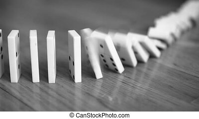 Close-up view of falling Dominoes. Black and white.