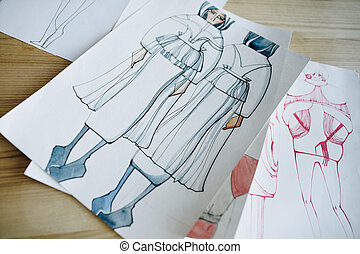 close-up view of fashion sketches on wooden table
