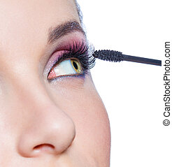 Close up view of female eye and brush applying mascara