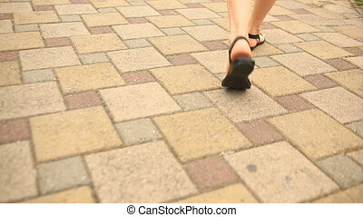Close-up view of female feet walking through the urban street. Female in sandals and shorts going in the city center.