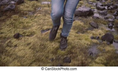 Close-up view of female foot in boots. Young woman walking...