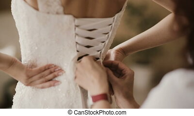 Close-up view of female hand helping bride to puts on dress. Bridesmaid lacing wedding dress on the back before ceremony
