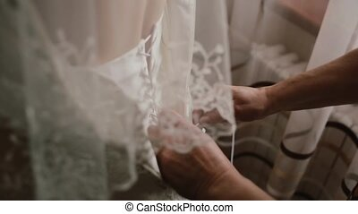 Close-up view of female hand helping bride to puts on the dress. Mother lacing wedding dress for her daughter. Back view
