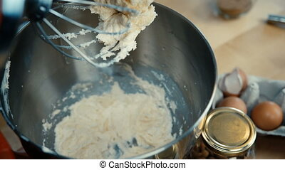 Close-up view of female hands adds the egg and turns on the mixer. Woman cooking the dough in the bowl on the kitchen.