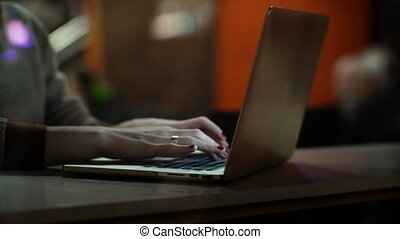 Close-up view of female hands typing on laptop. Businesswoman sitting on the table and using the computer.