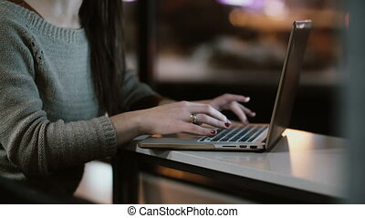 Close-up view of female hands typing on laptop computer keyboard. Young woman sitting on the table and working.