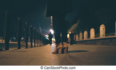 Close-up view of female legs wearing shoes on a high heel. Woman standing on the bridge in evening and waiting.