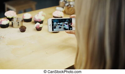 Close-up view of female taking photos of cupcakes with she...