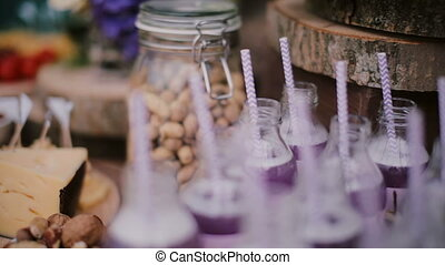Close-up view of food bar. Bottle with drinks standing on a wooden table. Candy bar.