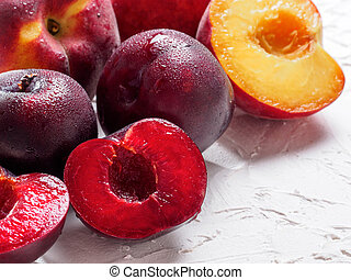 Close up view of fresh plum and peach on white concrete background