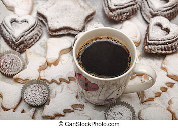Close up view of freshly baked new year cookies and hot coffee , selective focus , high angle