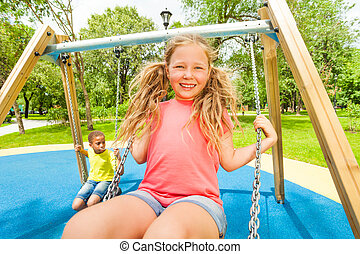 Close up view of girl swinging and boy behind