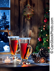 close up view of glass with mulled wine with gift boxes on color back