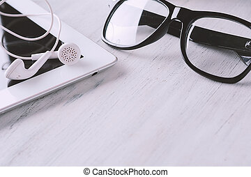 Close up view of glasses, tablet and earphones