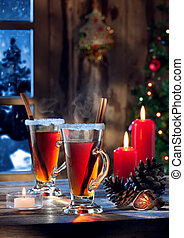 close up view of glasses with mulled wine with gift boxes on color back
