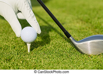 Close up view of golf ball on tee on golf course