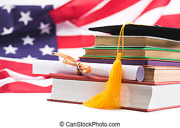 Close-up view of graduation mortarboard, books and diploma on us flag background, education concept