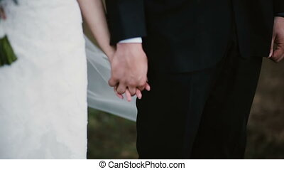 Close-up view of groom and bride holding hands on a wedding ceremony. Woman in wedding dress near man takes the bouqet.