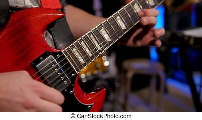 Close up view of guitarist plays electro guitar in night club