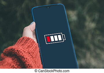 Close-up view of hand holding a smartphone with low battery on screen.